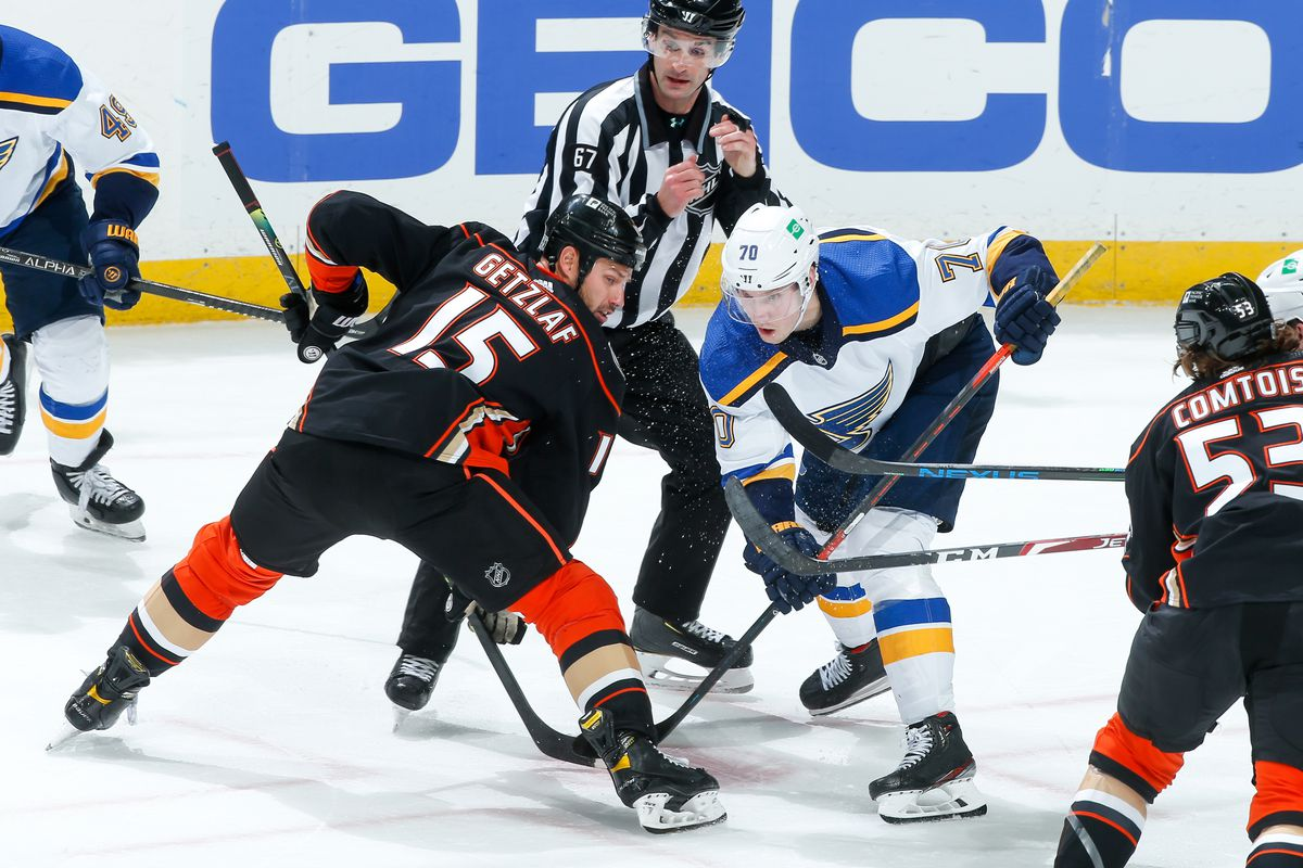 Ryan Getzlaf #15 of the Anaheim Ducks and Oskar Sundqvist #70 of the St. Louis Blues compete for a face-off as linesman Travis Gawryletz #67 looks on during the third period of the game at Honda Center on January 30, 2021 in Anaheim, California.