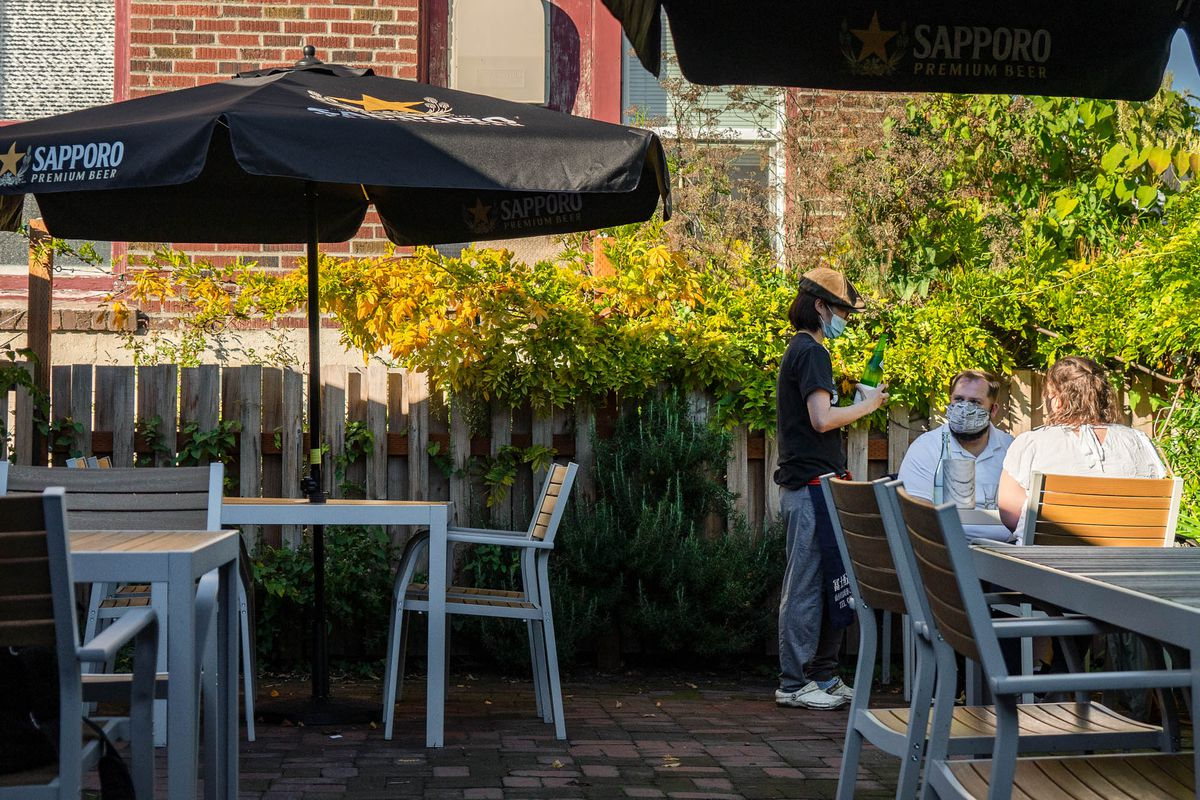 A couple sits on a patio in masks getting their order taken.