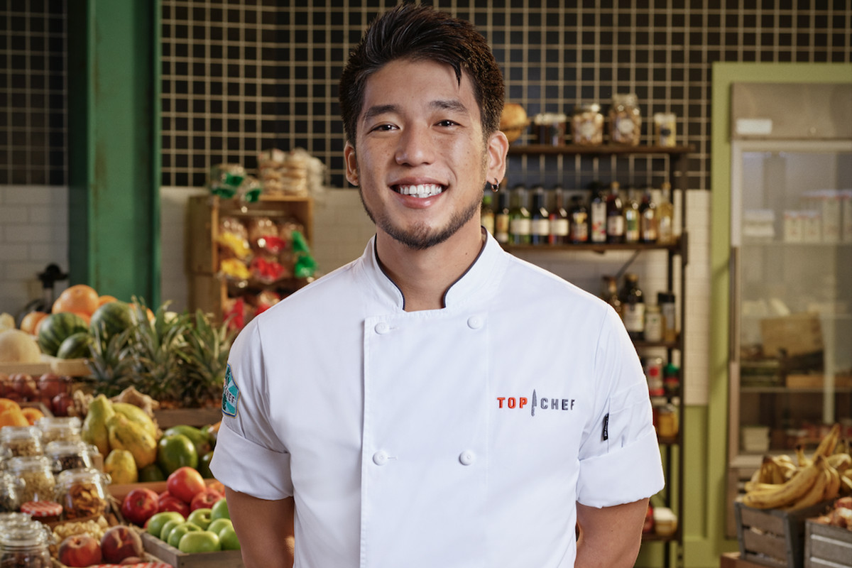"""A photo of Shota Nakajima in a """"Top Chef"""" apron with shelves of pantry items in the background"""