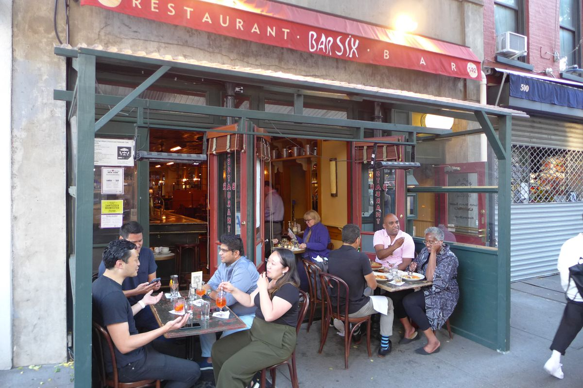 A red awning and two tables of diners sitting in front of the restaurant.