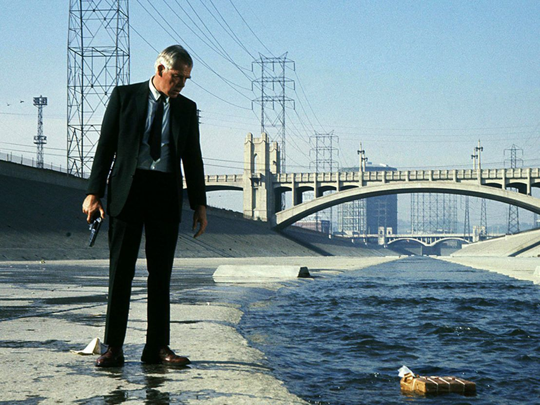 Lee Marvin as Walker holding a pistol and staring at a mysterious package floating in a ravine.