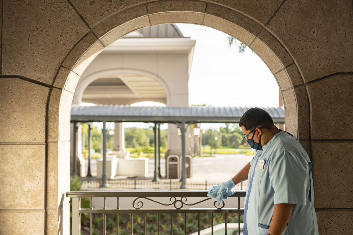 A worker wearing gloves and a mask cleans at Walt Disney World Resort in Lake Buena Vista, Florida.