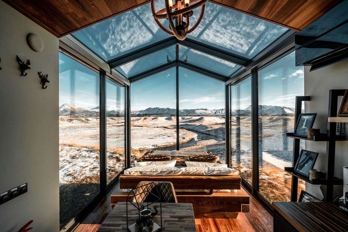 Interior of glass cabin with views to snowy landscape.