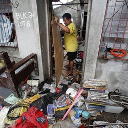 Edwin Dapon works to clean out his home in Tacloban, Friday, Nov. 22, 2013 following a typhoon.
