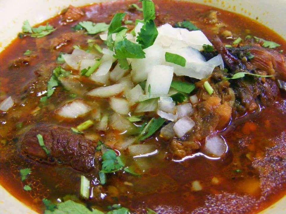 A close-up of a saucy birria Taco from Taqueria Las Cañadas