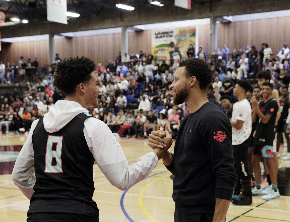 Stephen Curry shakes hands with his player Jalen Hood-Schifino (8) as he is introduced for the game at the Stephen Curry SC30 Select Camp at Merritt College in Oakland, Calif., on Wednesday, August 7, 2019.