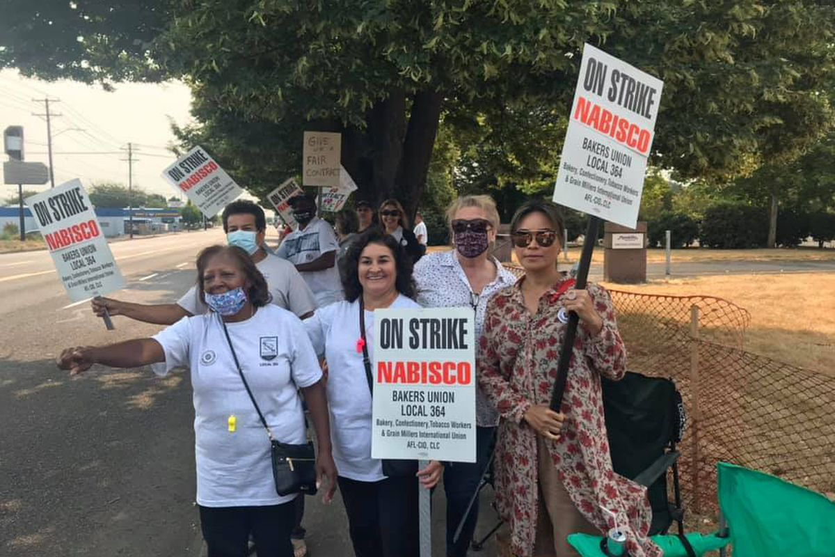"""A group of Nabisco workers and other Portlanders hold signs that read """"On Strike Nabisco,"""" standing on the side of the road in Portland, Oregon."""
