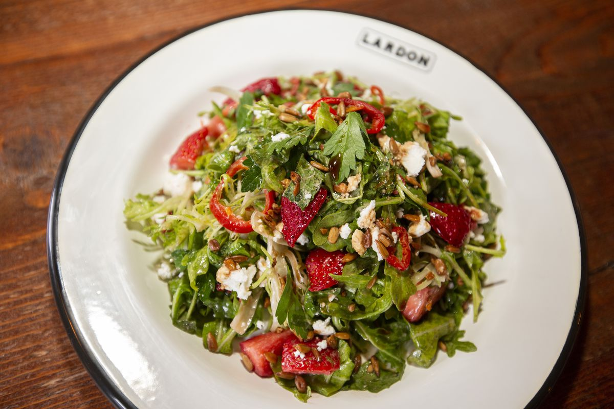 A round white plate holding a green salad with red strawberries.