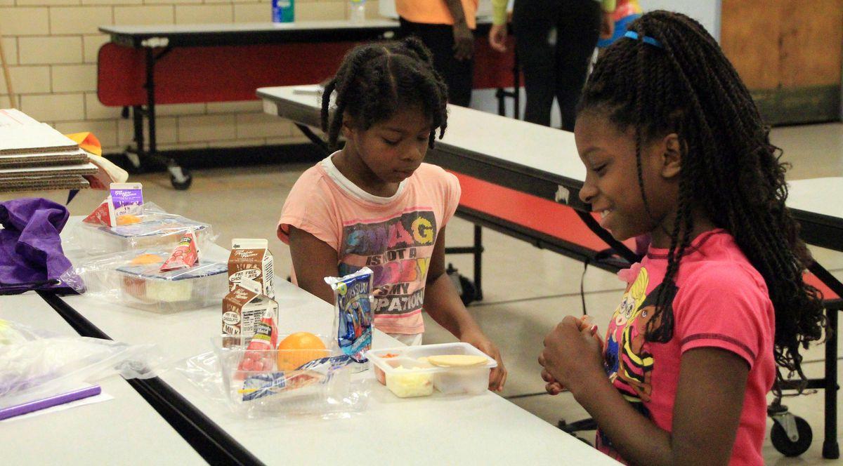 Markayla Mosby, 10, and Tatiana Watkins, 9, eat their lunch at Cummings Elementary School.