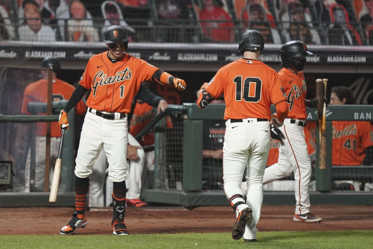 San Francisco Giants center fielder Mauricio Dubon congratulates third baseman Evan Longoria for hitting a ground ball to score first baseman Brandon Belt (not pictured) during the second inning of game two of a double header against the San Diego Padres at Oracle Park.