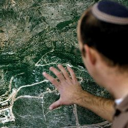 """FILE - In this Wednesday, Jan. 3, 2007 file photo, Israeli Amishai Shav-Tal, 31, one of the founders of the West Bank Jewish settlement of Bruchin looks at an aerial photo of the setllement. Israel legalized three unsanctioned West Bank settler outposts and was trying to save another on Tuesday April 24 2012. The Israeli government's announcement of its decision relied heavily on verbal gymnastics. It said it was """"formalizing the status"""" of Sansana, Bruchin and Rehalim, three longstanding enclaves that are home to hundreds of Jewish settlers."""