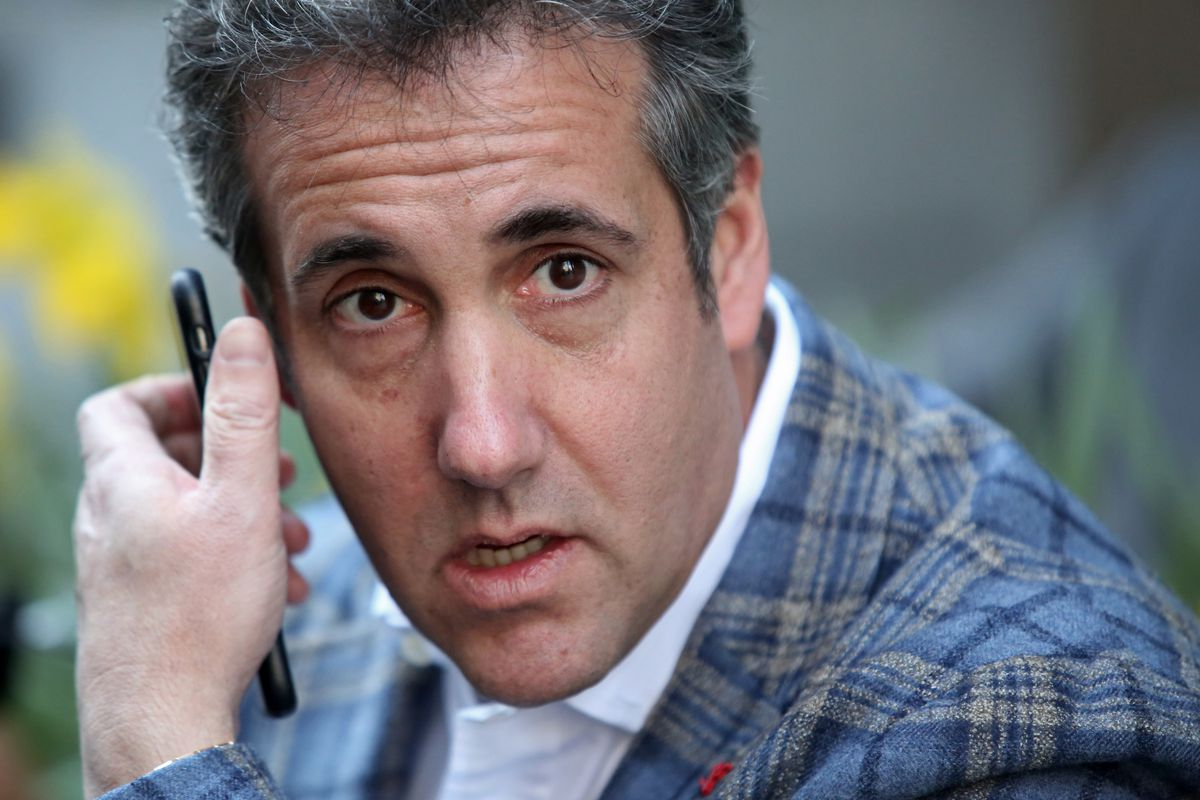 Former Trump lawyer Michael Cohen holding a cellphone up to his ear.