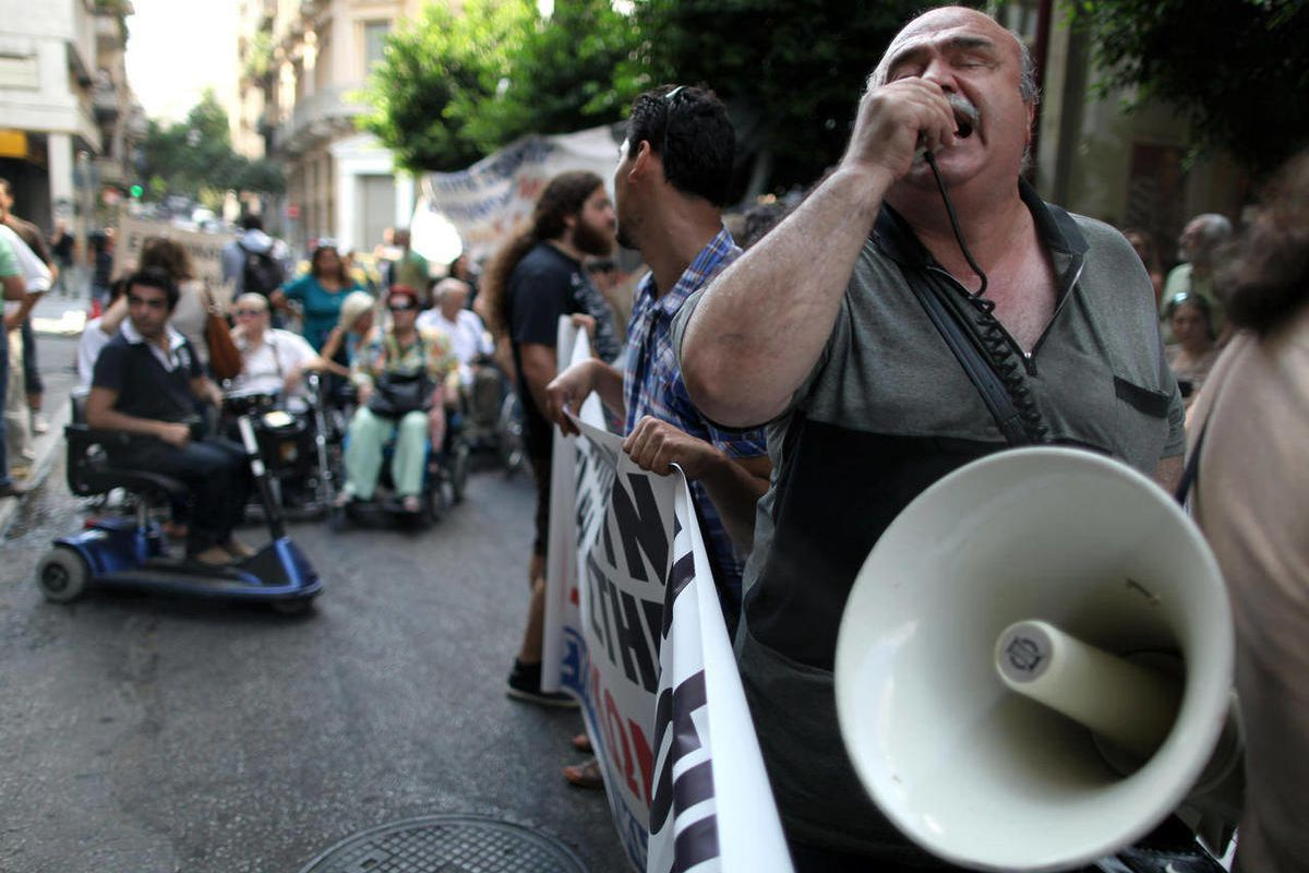 A disabled man chants slogans using a loudspeaker, outside the Finance Ministry in Athens, on Thursday, Sept. 13, 2012. Disabled groups are angry at likely benefit cuts under a major new austerity program demanded by international rescue creditors.