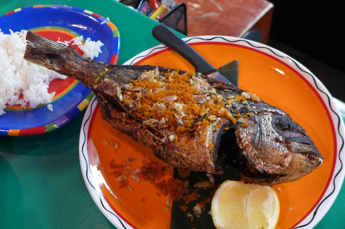 A whole fish with orange crumbs on top on an orange plate.