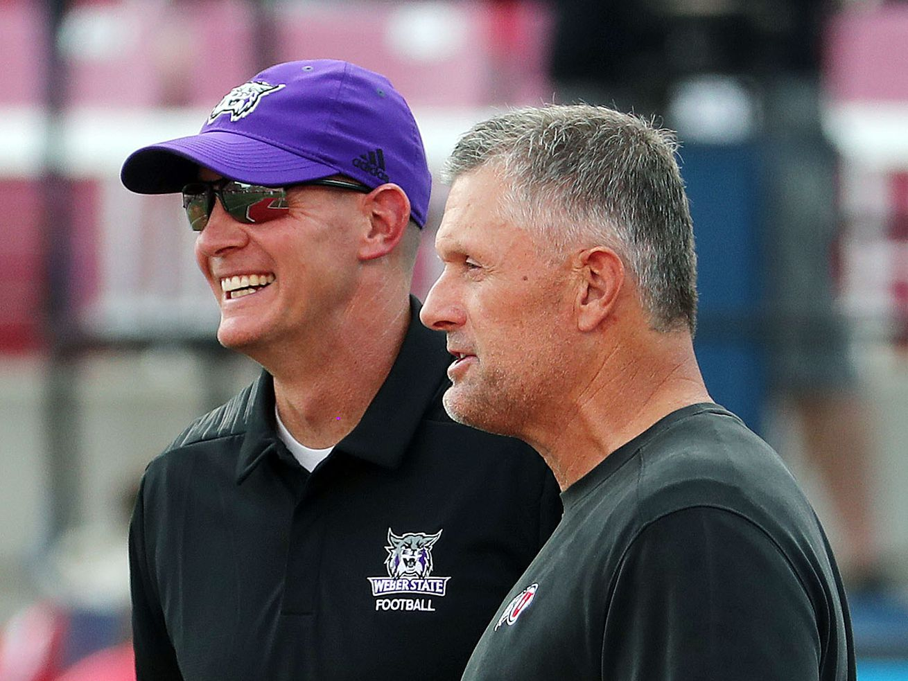 Utah Utes head coach Kyle Whittingham, right, and Weber State Wildcats head coach Jay Hill talk before NCAA football in Salt Lake City on Thursday, Aug. 30, 2018.