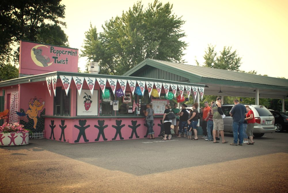 The pink Peppermint Twist building with people outside of it