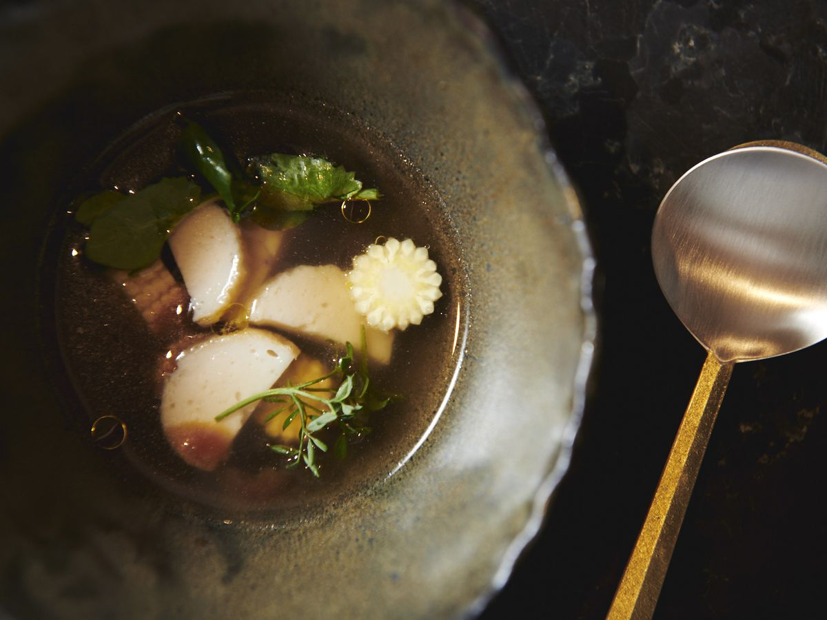 Guk soup with burdock, fish cakes, baby corn, and plum blossom fill a third of a dark, earthenware bowl