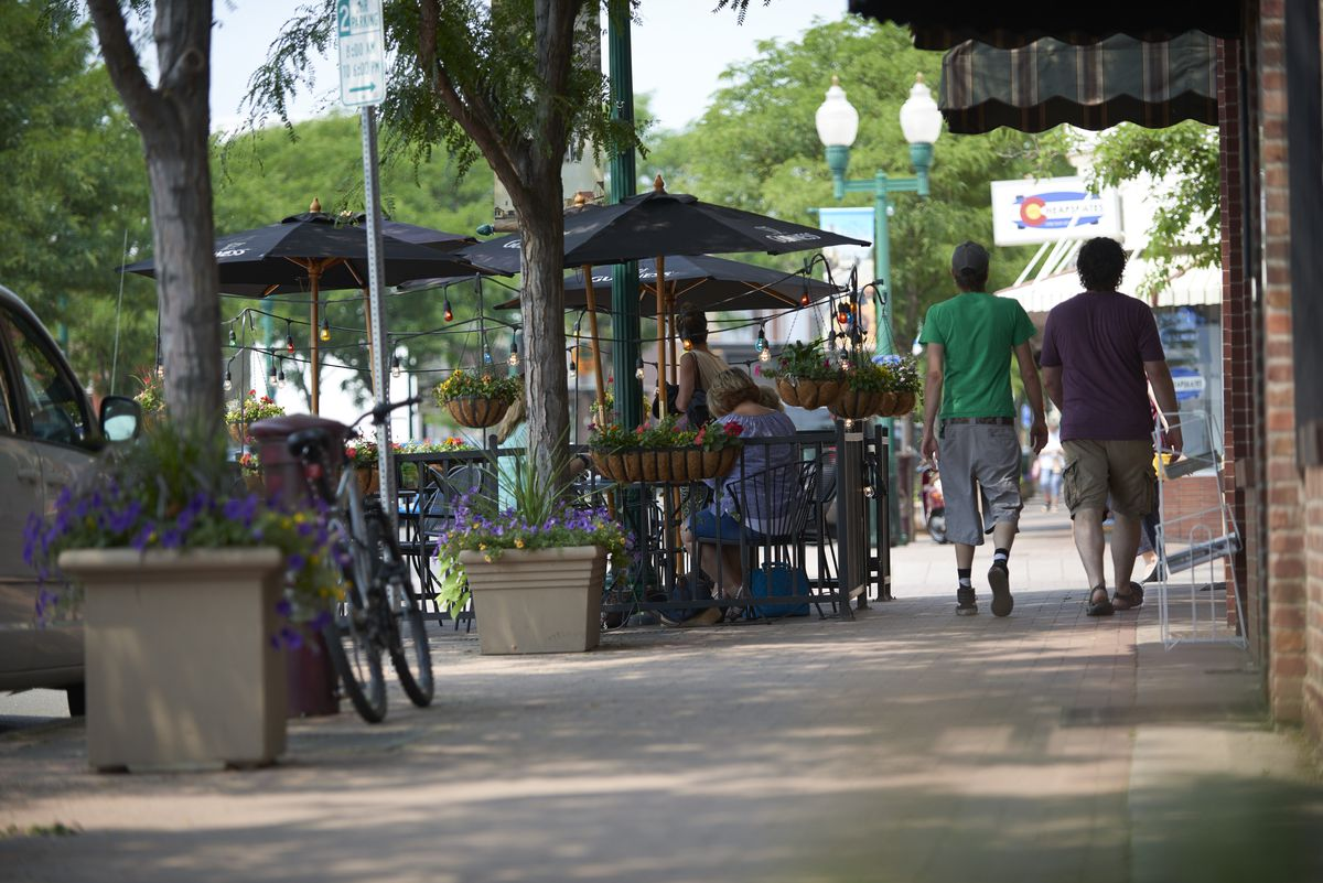 The sidewalk of a walkable downtown, lines with shops, street planters, and cafe tables.