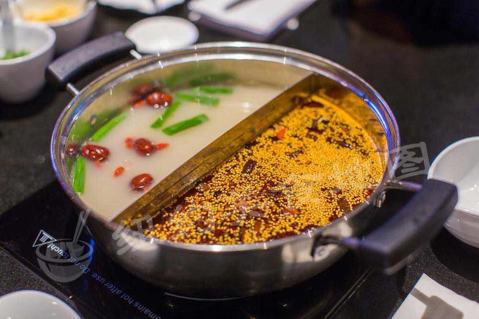A photo of a hot pot at D Station containing two types of broth