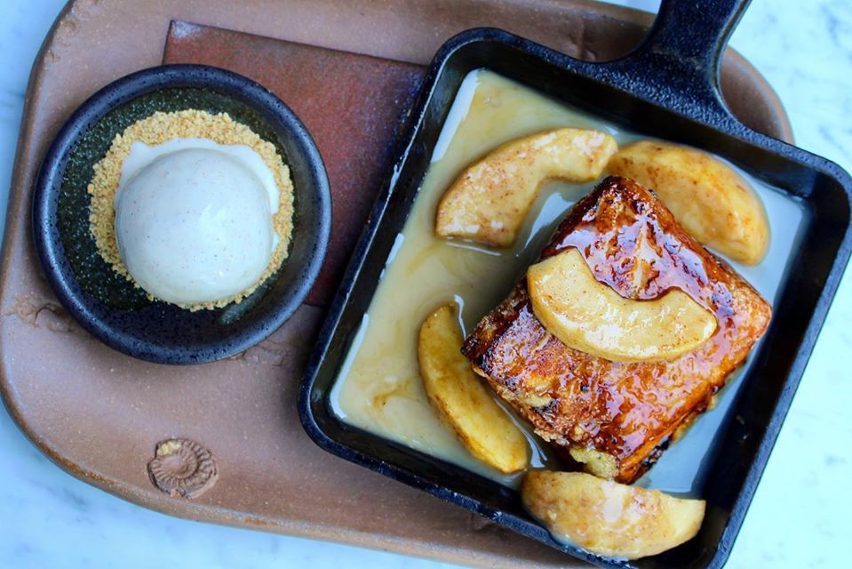 Dulce de leche soaked french toast with caramelized apples in a skillet
