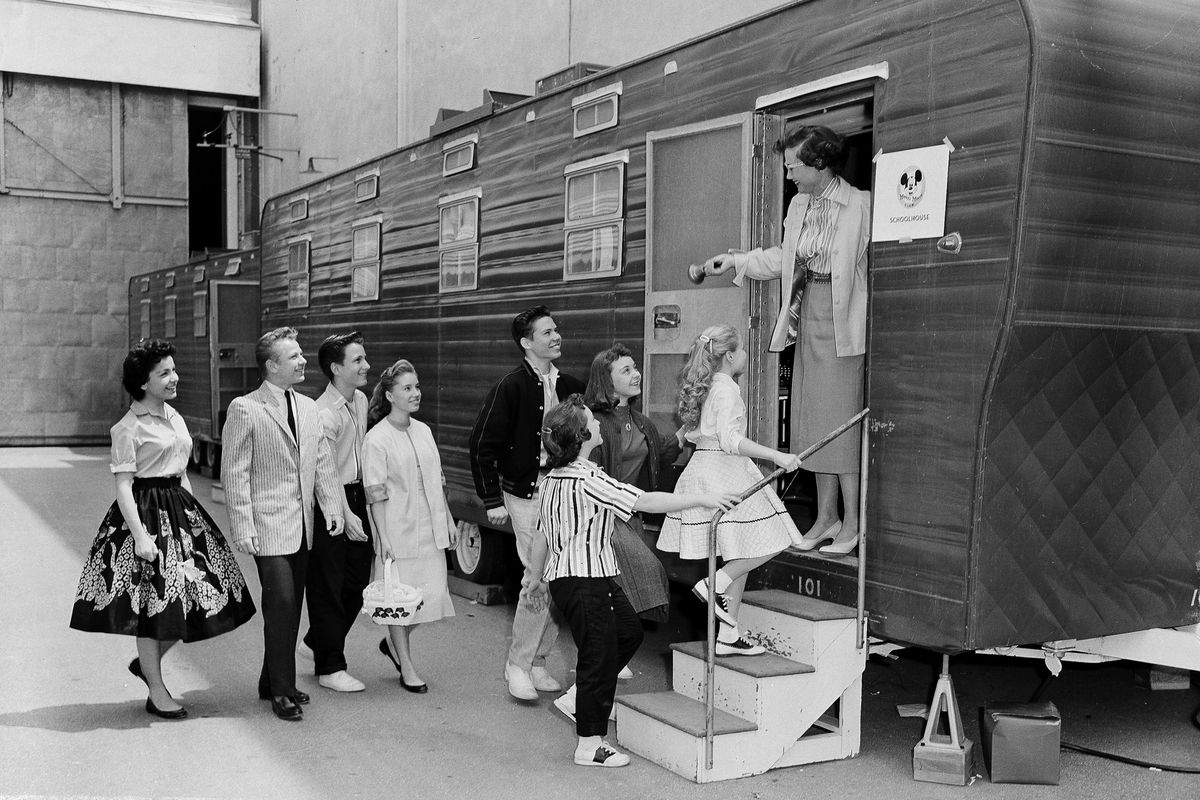 FILE - In this Aug 20, 1957, file photo, Walt Disney's Mouseketeers enter a large trailer that serves as their school on the Disney lot in Hollywood, Calif. Greeting them is their teacher Jean Seaman of the Los Angeles Public School System. Jimmy Dodd, re