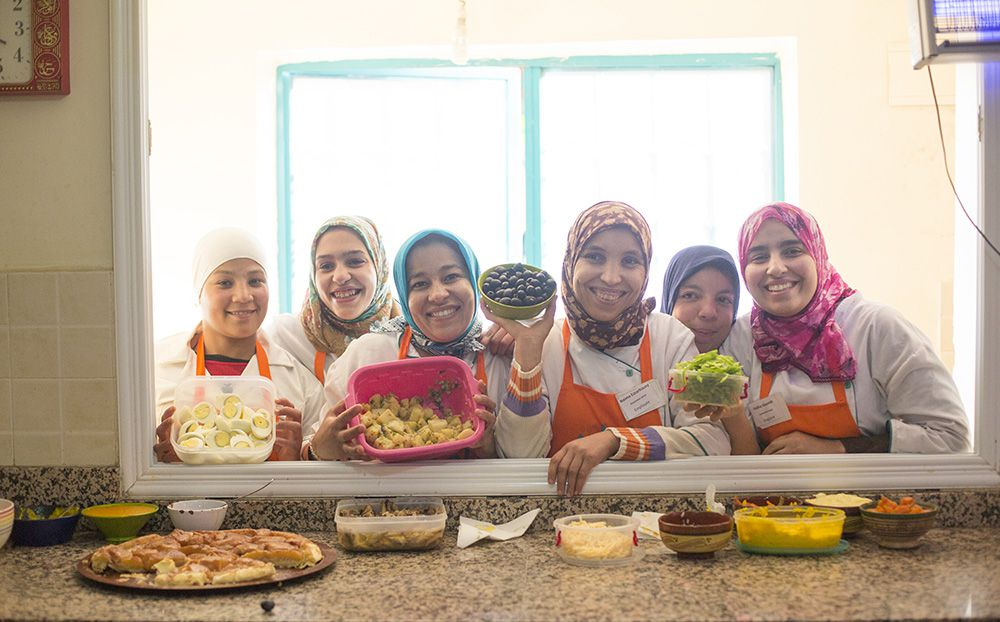 Six women lean over an interior window into a kitchen holding bowls of various ingredients including olives, eggs, and greens