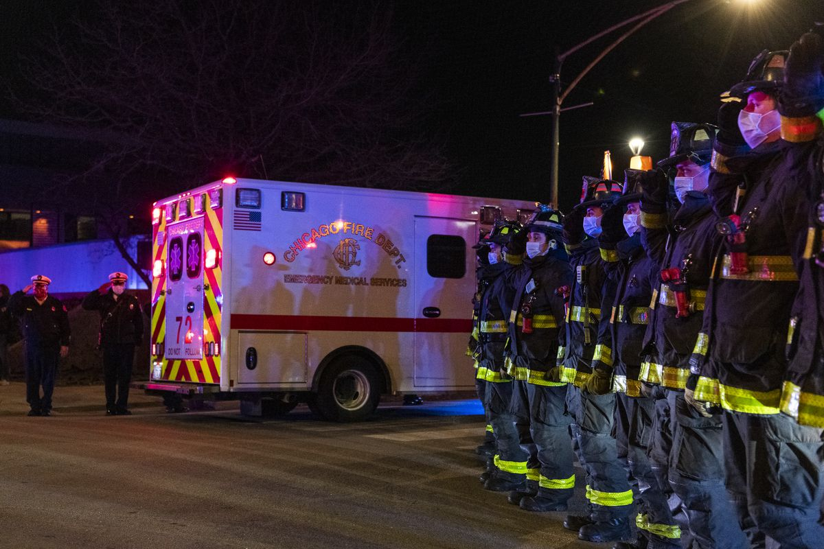 Chicago firefighters salute as the procession carrying the remains of retired firefighter Dwain Williams arrives at the Cook County Medical Examiners Office, after Williams was shot and killed in the 2400 block of West 118th St. in the Morgan Park Neighborhood, Thursday, Dec. 3, 2020.