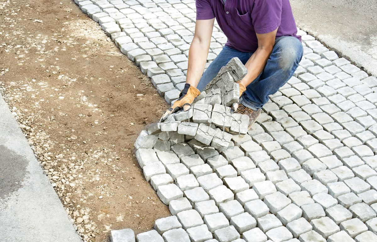 Man Lays Second Course Of Cobbles Of Driveway Apron