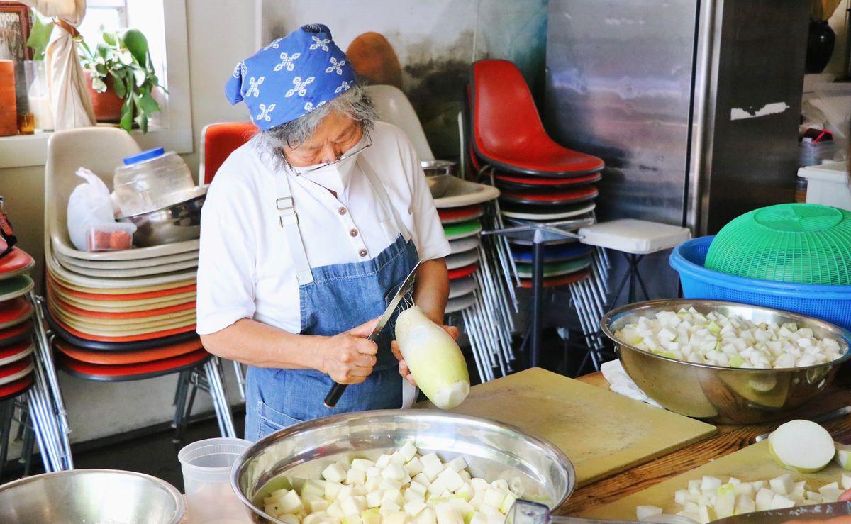 A chef slices Korean radish into large bowls