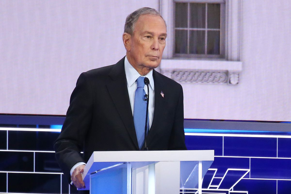Mike Bloomberg stands at a podium during a debate.