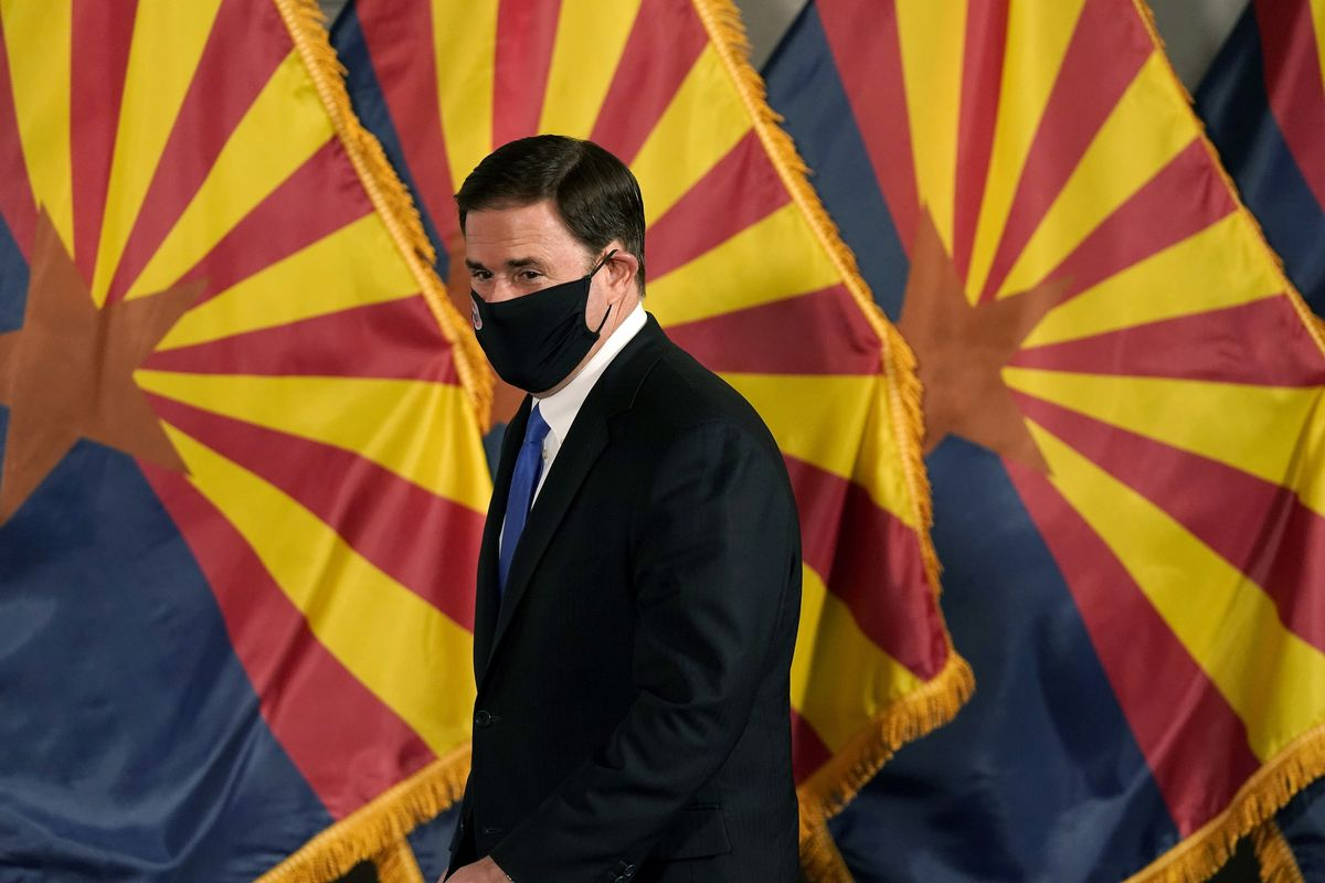 Arizona Republican Gov. Doug Ducey arrives for a news conference in Phoenix.