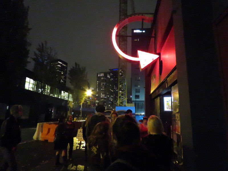 The exterior of a building at night with people lined up in front. A half-circle with an arrow at the bottom end points into the building, and is lit up red.