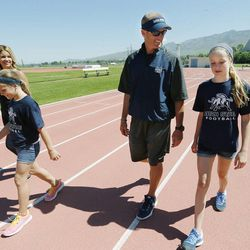 Utah State University football coach Matt Wells walks with his daughters Ella and Jadyn and wife Jen during a kids football camp in Logan Friday, June 12, 2015.