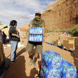 Chad Valentine carries bottled water while volunteering at a drive-thru food bank, organized by Transitions Pantry, in Oljato-Monument Valley, San Juan County, on Thursday, April 30, 2020. The Navajo Nation has one of the highest per capita COVID-19 infection rates in the country.