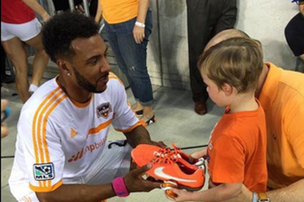 Giles Barnes gives a pair of his boots to Bennett Nester prior to the game against New England.