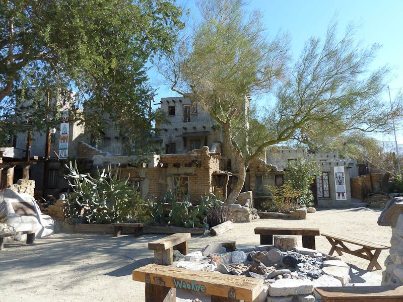 In the foreground is a courtyard with a fire pit. In the background is a building next to desert trees.