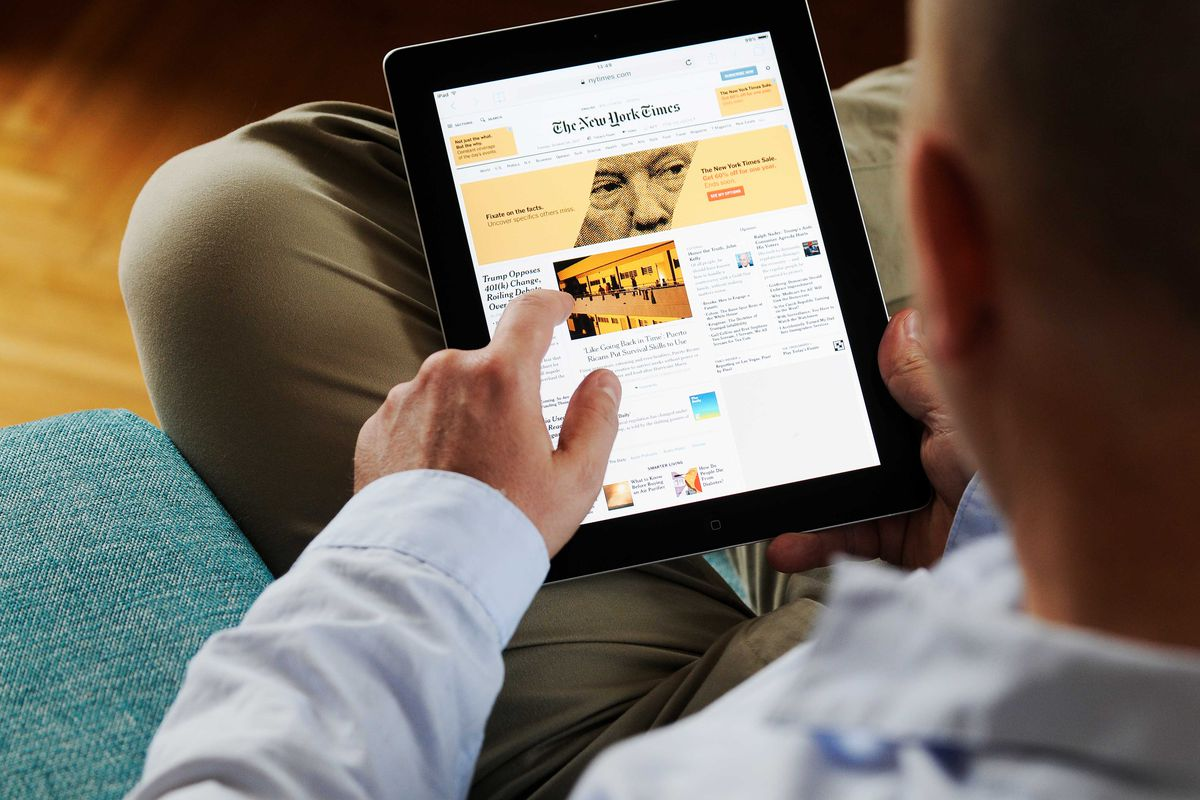 A man looks at the New York Times app on an iPad.