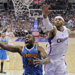 New Orleans Hornets forward Carl Landry, left, shoots as Los Angeles Clippers forward Kenyon Martin defends during the first half of their NBA basketball game, Sunday, April 22, 2012, in Los Angeles.