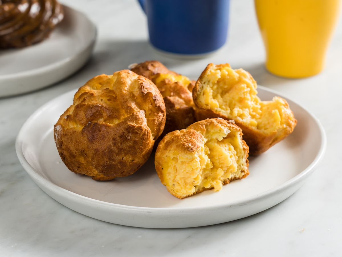 A close-up photo shows a plate of egg gougères, with one broken apart to display scrambled eggs inside.