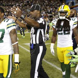 An official gestures as Green Bay Packers cornerback Sam Shields (37), safety Jerron McMillian (22) and Seattle Seahawks free safety Earl Thomas (29) leave the field in the second half of an NFL football game, Monday, Sept. 24, 2012, in Seattle. After a period of confusion, a Seahawks touchdown by wide receiver Golden Tate was allowed to stand for the 14-12 win.