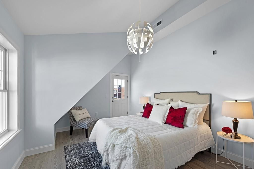 A small bedroom with a bed and a window, and part of the wall is jutting out.