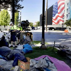 Construction of the 360 Apartments progresses as Salt Lake City police officers ticket a homeless woman for smoking marijuana in Pioneer Park on Wednesday, Sept. 28, 2016.  The construction of the six-floor 151-unit project is located directly west of Pioneer Park.