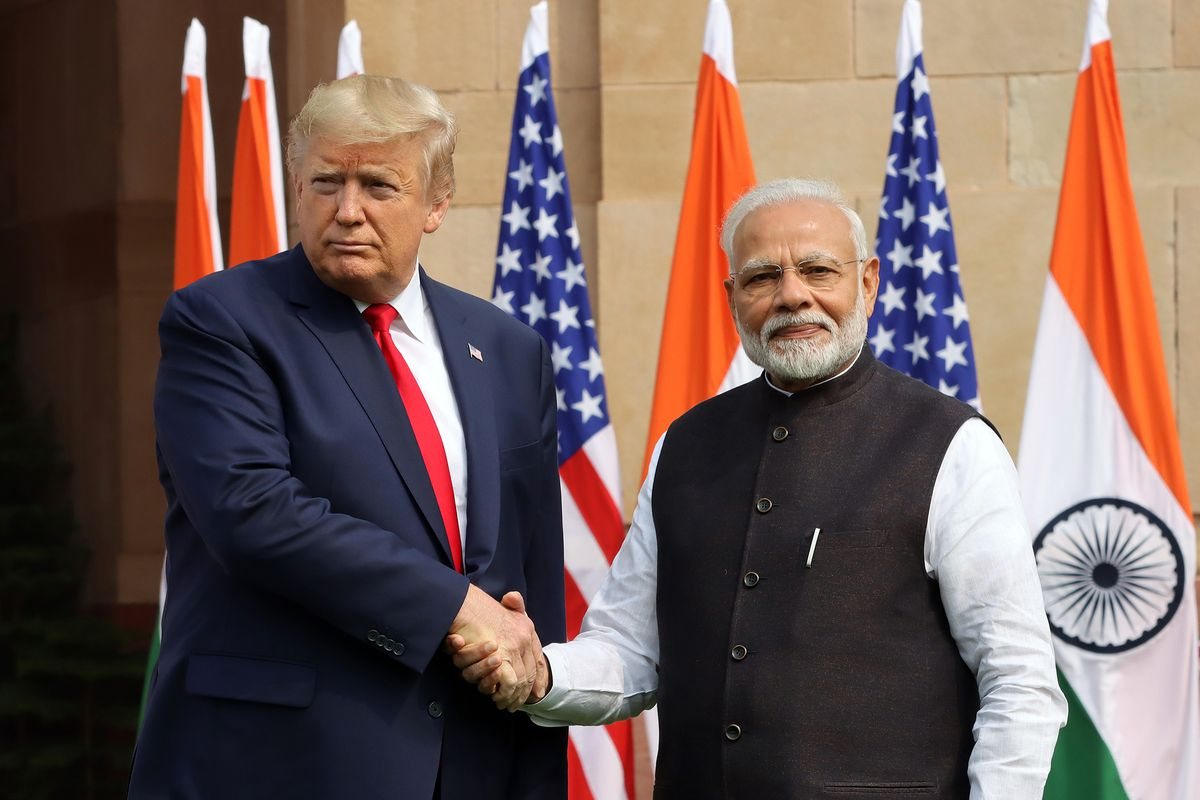 Donald Trump and Narendra Modi shaking hands while standing in front of US and Indian flags.