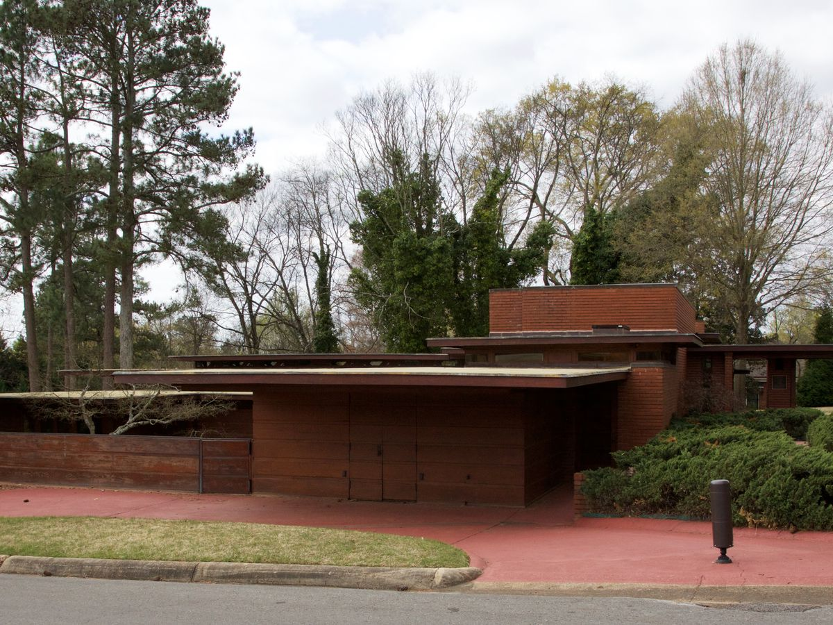 Rosenbaum House by Frank Lloyd Wright. The facade is wood and the roof is flat. There are trees in the background.