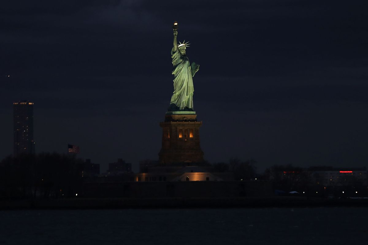 The Sun Sets Behind The Statue Of Liberty