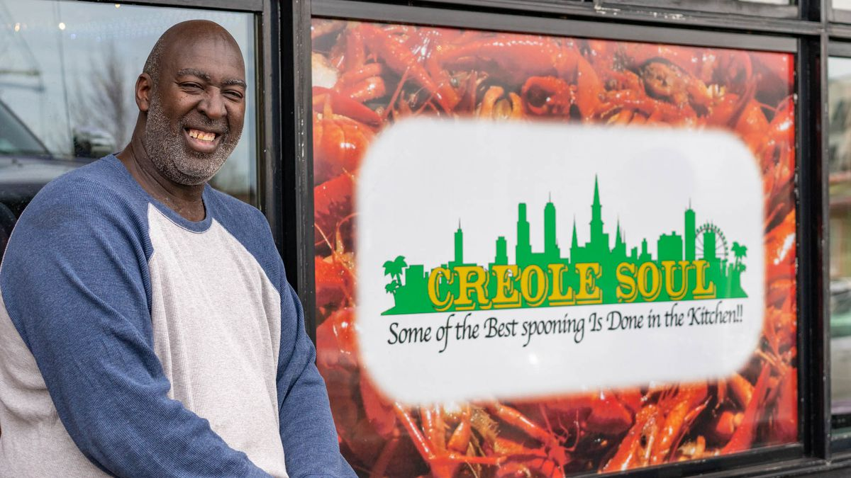 """Hampton Isom sits next to the sign for his restaurant in Des Moines, Washington, which reads """"Dat Creole Soul: Some of the best spooning is done in the kitchen"""""""