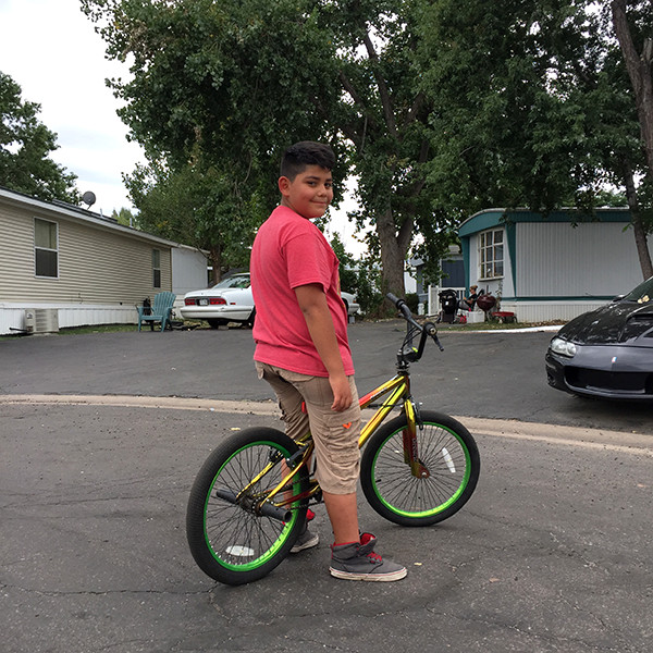 Emmanuel Zamudio, 9, rides his bike in his mobile home community in August before school starts.
