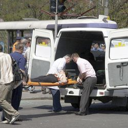 People assist injured after an explosion in Dnipropetrovsk, Ukraine, Friday, April 27, 2012.  Ukraine officials say dozens of people including schoolchildren, were injured in four blasts in the eastern Ukrainian city.