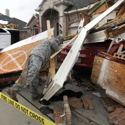 Texas Army National Guard Cpl. Brock Fischer of Charlie Troop, 3-124 Cav., searches a vehicle in front of a tornado damaged home Tuesday, April 3, 2012, in Forney, Texas. Tornadoes tore through the Dallas area Tuesday, peeling roofs off homes, tossing big-rig trucks into the air and leaving flattened tractor trailers strewn along highways and parking lots.