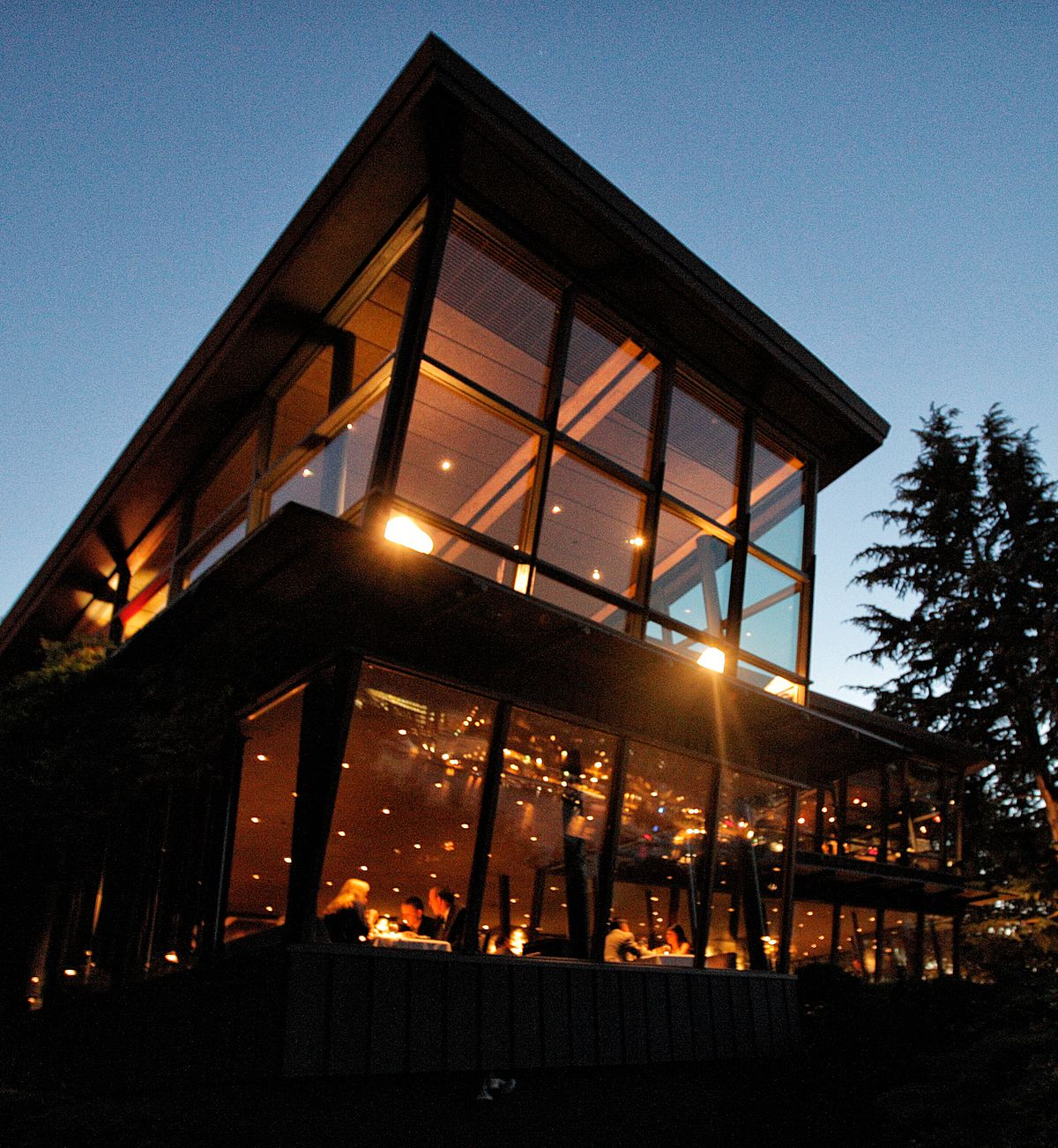 The exterior of Canlis restaurant at night with the dining room lit up
